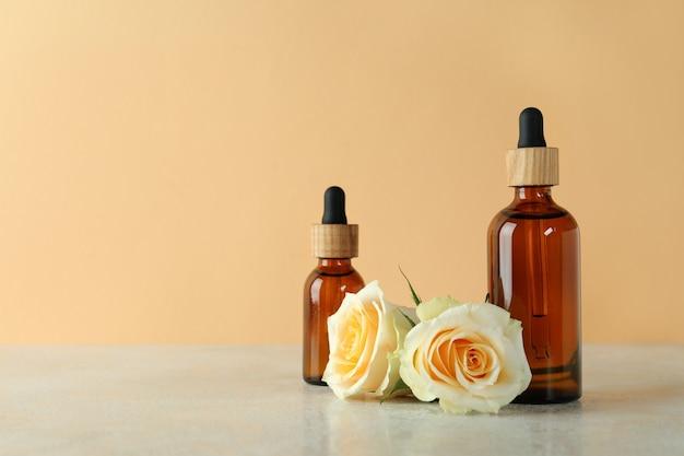 Бутылки с эфирным маслом розы и розами на фоне бежевого
