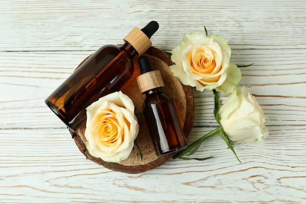 Бутылки с эфирным маслом розы и розами на белом деревянном столе