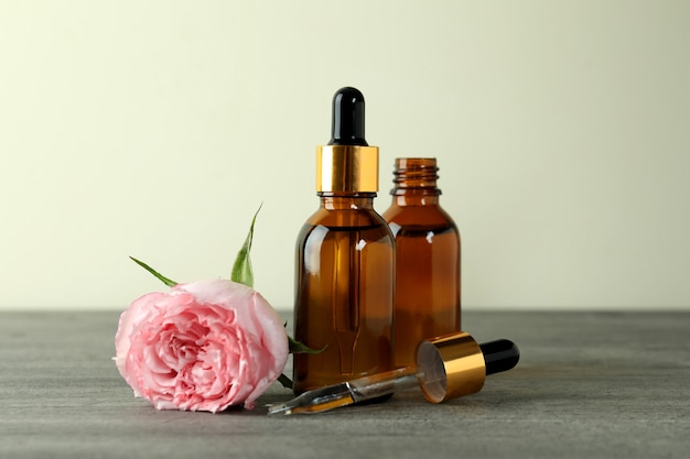 Bottles with rose essential oil on gray textured table