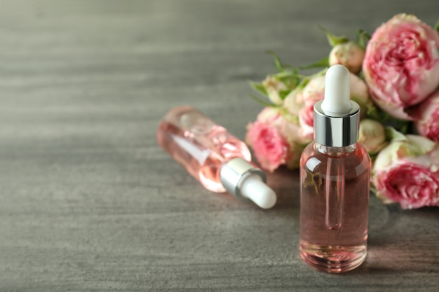 Bottles with rose essential oil on gray textured