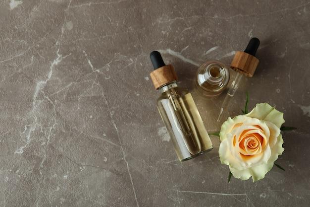 Бутылки с эфирным маслом розы на сером текстурированном