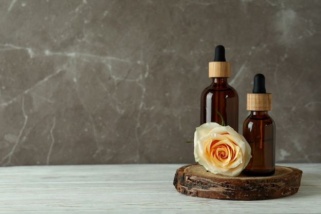 Bottles with rose essential oil and rose on white wooden table
