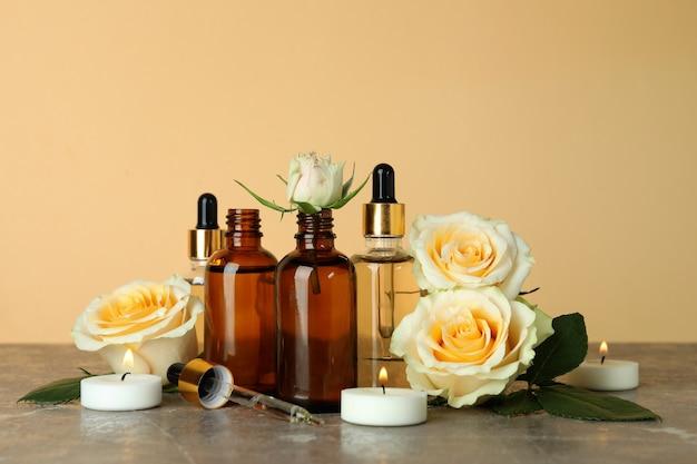 Бутылки с эфирным маслом розы, розы и свечи на фоне бежевого
