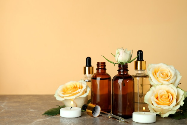 Bottles with rose essential oil, roses and candles against beige