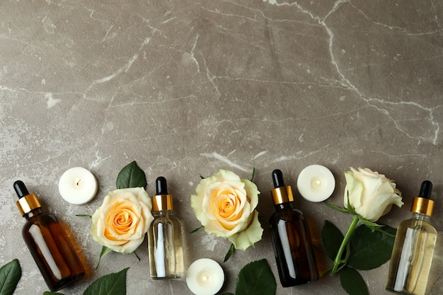 Bottles with rose essential oil, roses and candles on gray textured