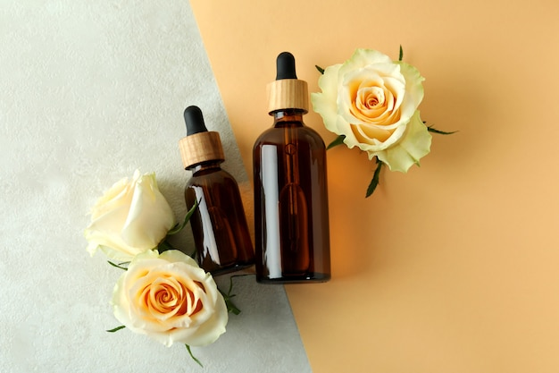 Bottles with rose essential oil and roses on two tone