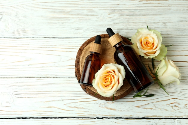 Bottles with rose essential oil and roses on white wooden table