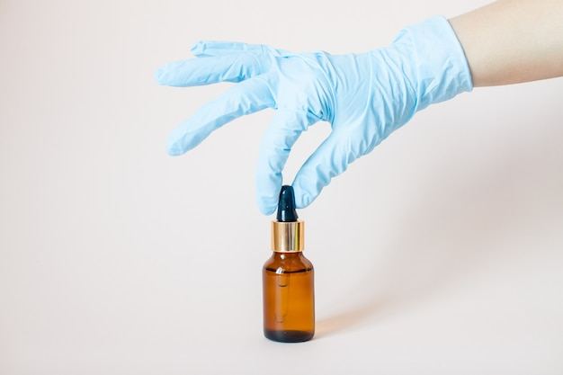 Bottles with serum for the face in his hands in protective medical rubber gloves on gray