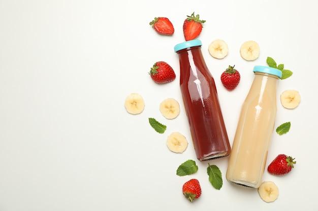 Бутылки с клубничным и банановым соком на белом