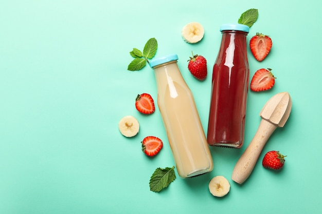 Bottles with strawberry and banana juices on mint