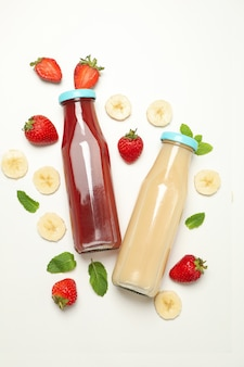 Bottles with strawberry and banana juices on white