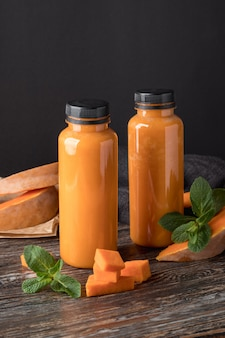 Bottles with tasty pumpkin smoothie on wooden table