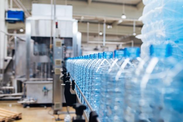Завод по розливу - линия розлива воды для обработки и розлива чистой родниковой воды в синие бутылки. выборочный фокус.
