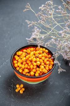 Vista dal basso l'olivello spinoso nel ramo di fiori essiccati ciotola su superficie rosso scuro dark