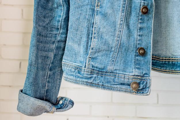 Bottom of blue denim woman jacket. clothes fragment