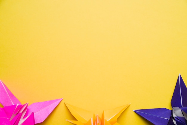 Bottom border decorated with colorful origami paper flowers on yellow background