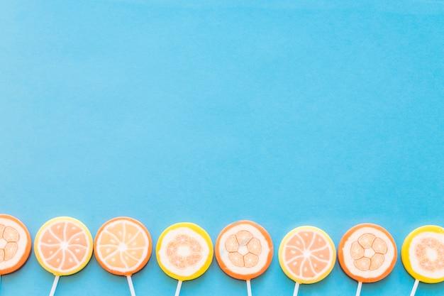 Bottom border of jelly lollipops over blue background