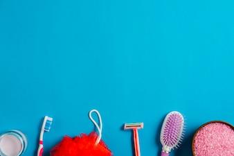 Bottom border made with hairbrush; cream; toothbrush; razor; bath puff and salt on blue backdrop