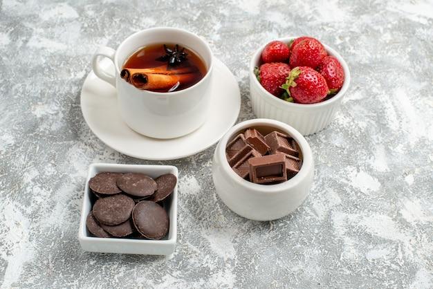 Vista ravvicinata dal basso ciotole con fragole e cioccolatini cannella tè ai semi di anice sul terreno grigio-bianco