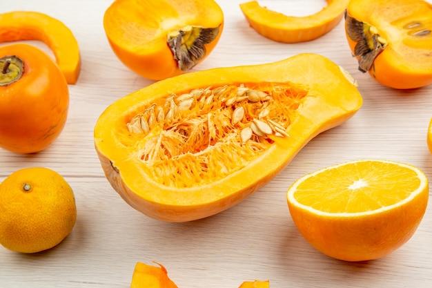 Vista ravvicinata dal basso zucca tagliata a metà mandarino di cachi su un tavolo di legno bianco