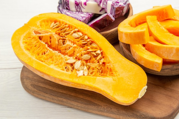 Bottom close view butternut squash cut in half red cabbage and squash slices in bowls on cutting board on white table