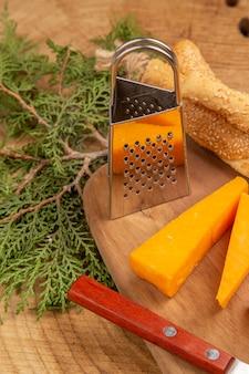 Vista ravvicinata dal basso coltello da pane e formaggio piccola grattugia su tagliere rami di pino su superficie di legno