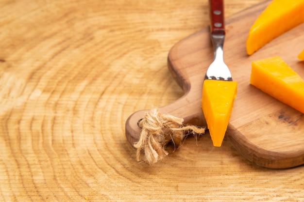 Vista ravvicinata dal basso formaggio su forchetta fette di formaggio su tagliere su tavola di legno