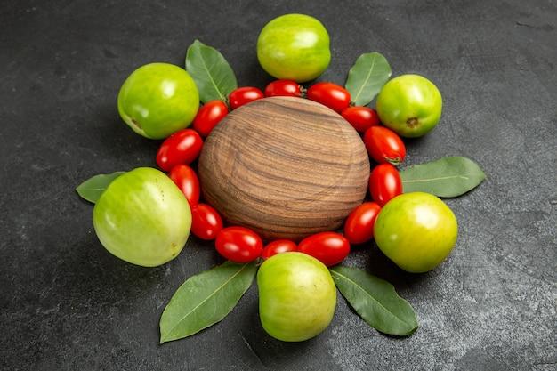 Vista ravvicinata inferiore pomodorini pomodori verdi e foglie di alloro intorno a un piatto di legno su sfondo scuro