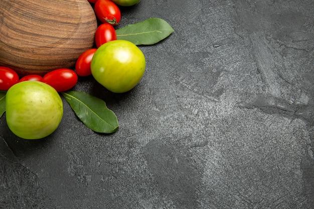 Vista ravvicinata dal basso pomodorini pomodori verdi e foglie di alloro intorno a un piatto da portata in legno su sfondo scuro