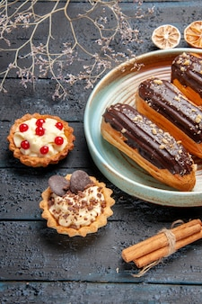 Bottom close view chocolate eclairs on oval plate dried flower branch tarts and cinnamon on the dark wooden table