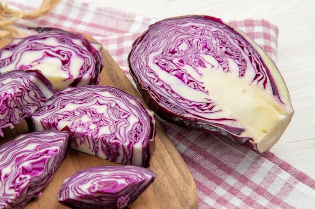 Bottom close view chopped red cabbage knife on wooden board on pink white checkered kitchen towel on grey table