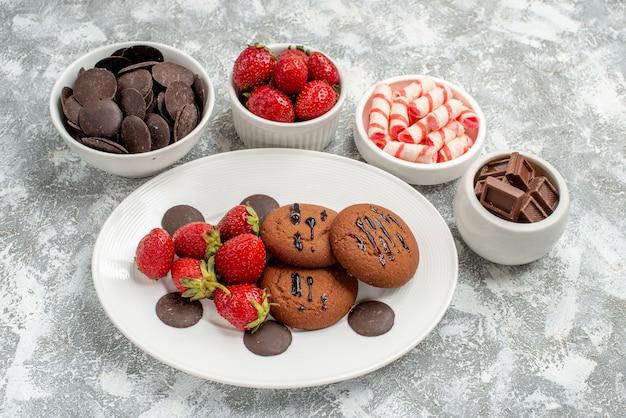 Vista ravvicinata dal basso biscotti fragole e cioccolatini rotondi sul piatto ovale bianco circondato ciotole con caramelle fragole e cioccolatini a terra con spazio di copia