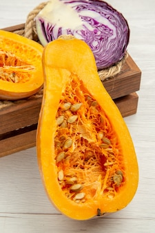 Bottom close view cut butternut squash cut red cabbage in wooden box on white table