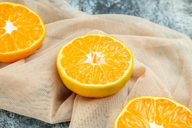 Bottom close view cut oranges on beige shawl on dark surface