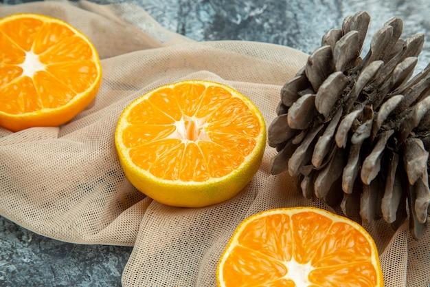 Bottom close view cut oranges pinecones on beige shawl on dark surface