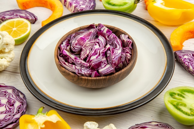 Vista ravvicinata dal basso tagliare i cavoli rossi in una ciotola su un piatto rotondo tagliare le verdure su una superficie bianca