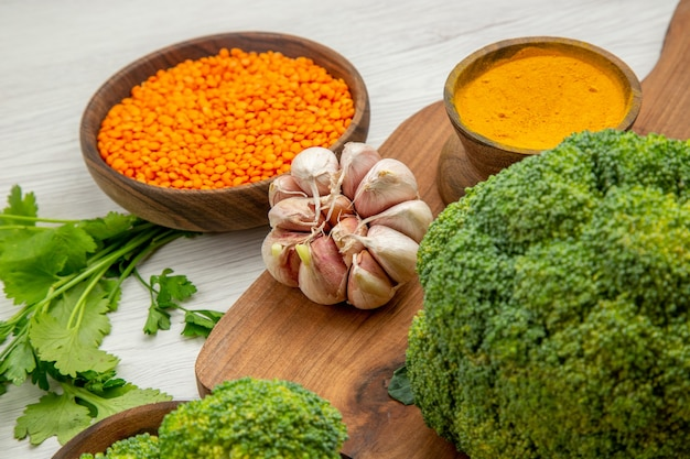 Bottom close view fresh broccoli garlic turmeric on cutting board parsley lentile bowl on grey table