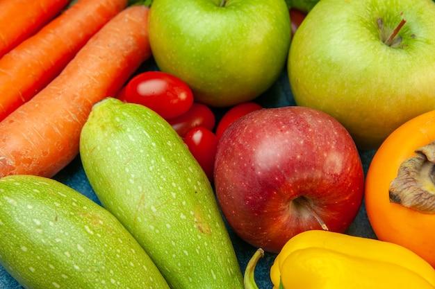 Вид снизу крупным планом, фрукты и овощи, помидоры черри, яблоко, хурма, кабачки, морковь на синем столе