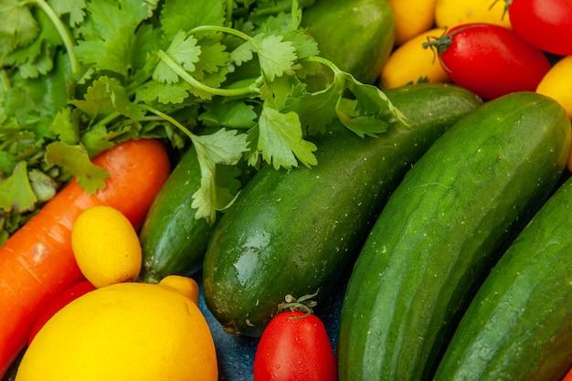 Vista ravvicinata in basso frutta e verdura prezzemolo pomodorini cumcuats cetrioli limone carota
