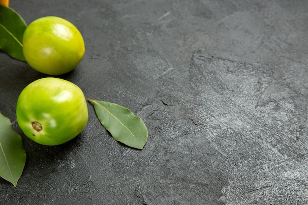 Bottom close view green tomatoes bay leaves on dark background