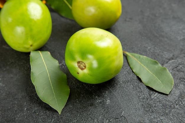 Vista ravvicinata dal basso dei pomodori verdi foglie di alloro su sfondo scuro