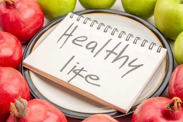 白いテーブルの上のプレート上のノートに書かれた下のクローズビューザクロ青リンゴの健康的な生活