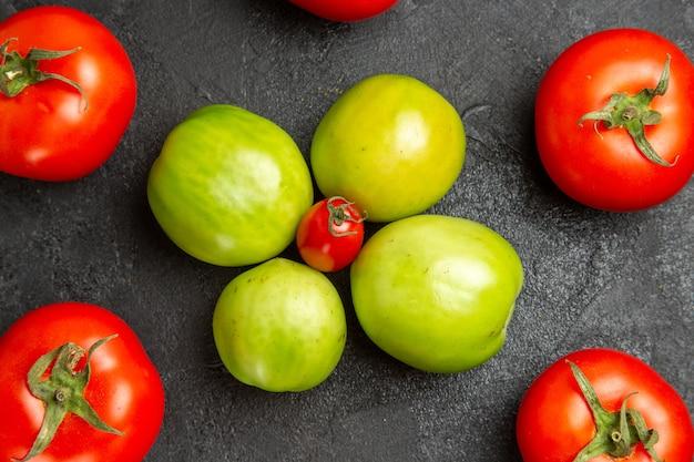 暗いテーブルの上のチェリートマトの周りの赤と緑のトマトを下から見た図