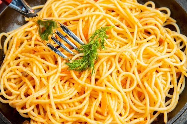Vista ravvicinata dal basso spaghetti padella tovaglia a quadretti rossa e bianca su sfondo scuro