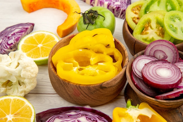 Bottom close view wooden bowls with cut vegetables cauliflower onion red cabbage green tomato on white wooden surface