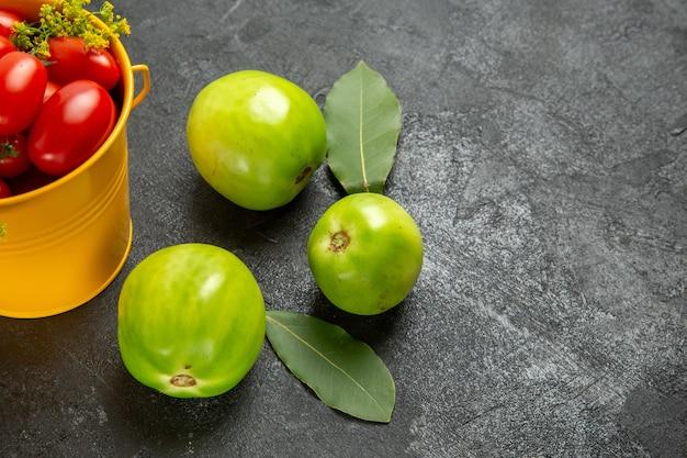 체리 토마토와 딜 꽃 베이 잎과 어두운 배경에 녹색 토마토로 가득한 하단 닫기보기 노란색 양동이