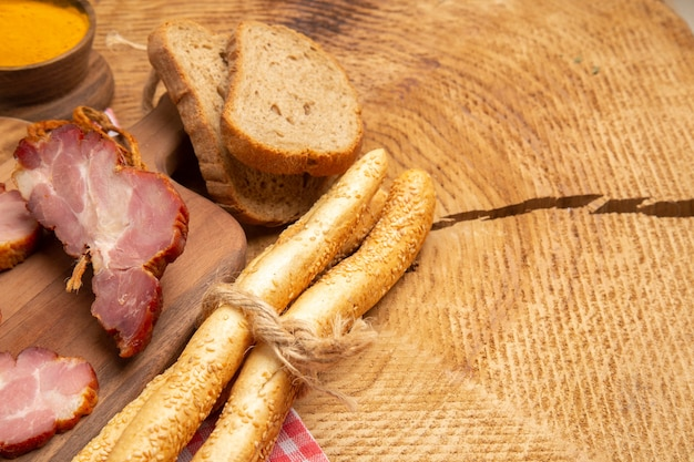 Mezza vista inferiore fette becon sul tagliere pane bianco e marrone curcuma in una piccola ciotola su tavola di legno