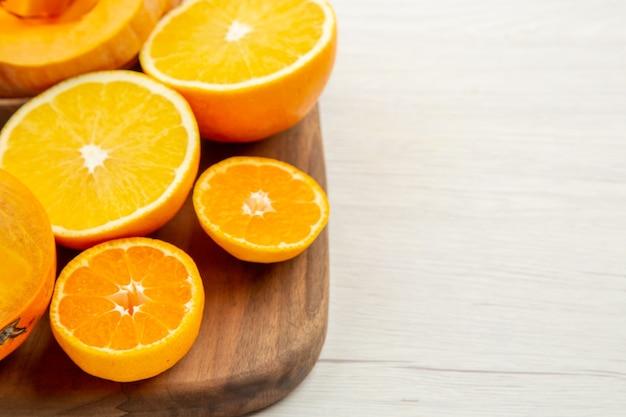 ボウルの下半分のビューバターナッツスカッシュは、白いテーブルの空きスペースのまな板に柿みかんとオレンジをカットします