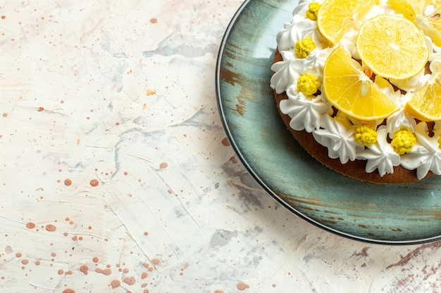 Torta a metà vista inferiore con crema pasticcera bianca e fette di limone su piatto rotondo su tavolo grigio chiaro