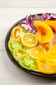 下半分のビューみじん切り野菜と果物パンプキンピーマングリーントマト赤キャベツ白い表面の黒いプレートに 無料写真
